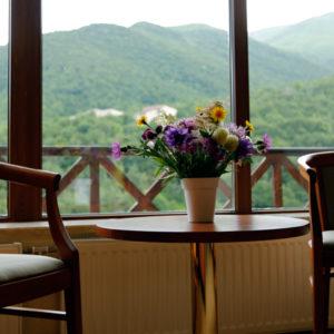 Два стула и маленький столик с цветами рядом с окном. Из окна вид на горы. фото