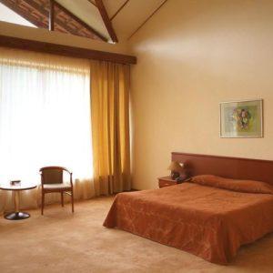 Номер в отеле с двухместной кроватью, две тумбочки, большое окно завешено, фото